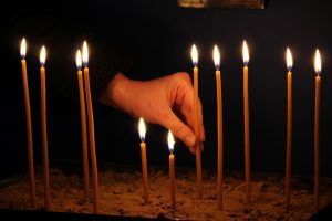 Hand with lit candle.